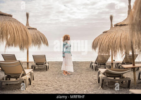 centered position beautiful caucasian middle age woman freedom in outdoor leisure activity at the beach with ocean and clouds in the sky. seats and um - Stock Photo
