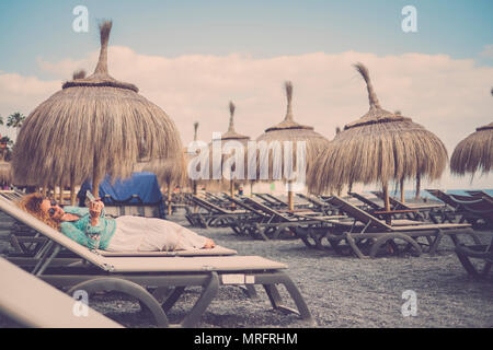 beautiful caucasian female middle age lay down on the seats at the beach with tropical umbrellas. travel and vacation rest concept. stay connected wit - Stock Photo