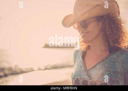 beautiful and wonderful blonde curly hair model middle age with cowboy hat smile and pose at the beach with golden sunset in the background. colored a - Stock Photo