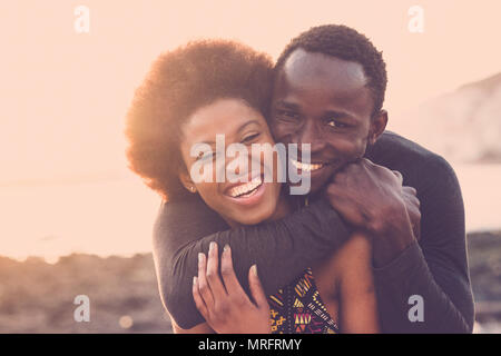 beautiful black race nice model couple man and woman young age hug and stay together with love and friendship. outdoor scenic place near the beach for - Stock Photo