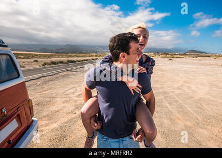 nice caucasian beautiful model couple in love play and stay together in leisure activity outdoor near a long road crossing the desert in a long trip v - Stock Photo