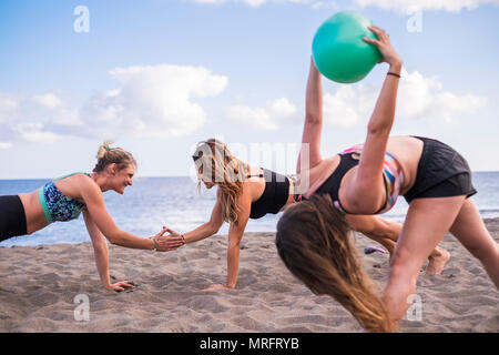 group of females people caucasian three beautiful women doing yoga and fitness on the sand at the beach near the ocean. freedom concept for leisure ac - Stock Photo