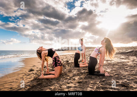pilates classes and lesson for group of people at the beach. three young beautiful model women doing fitness on the shore near the ocean water. wonder - Stock Photo
