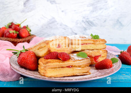Sweet tasty puff pastry dessert on plate on wooden background. Delicious homemade cookies with strawberry jam, berries and sugar powder. - Stock Photo