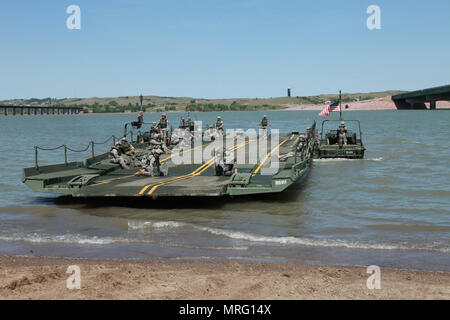 U.S. Army Soldiers with the 200th Engineer Company, South Dakota Army National Guard, prepare to load military vehicles from the Kansas Army National Guard on to an Improved Ribbon Bridge during a river crossing operation in support of Golden Coyote, Chamberlain, S.D., June 10, 2017. The Golden Coyote exercise is a three-phase, scenario-driven exercise conducted in the Black Hills of South Dakota and Wyoming, which enables commanders to focus on mission essential task requirements, warrior tasks and drills. - Stock Photo