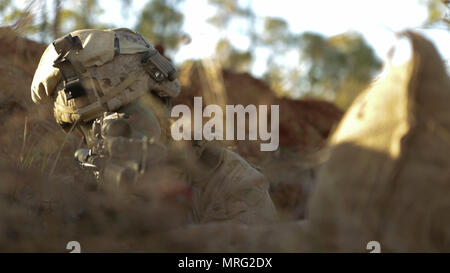 "NORTHERN TERRITORY, Australia – Lance Cpl. Andrew Naranjo, a rifleman with 2nd platoon, Lima Company, 3rd Battalion, 4th Marine Regiment, sets up security inside his fighting hole, June 5th, 2017. ""We're preparing for any fight that may occur,"" said Naranjo, a Sylmar, California native. - Stock Photo"