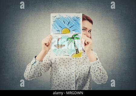 Happy businesswoman hiding face behind a white paper sheet with an exotic place drawn. Dreaming about vacation on the seaside. - Stock Photo