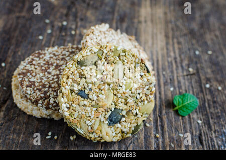 Dessert cereal snacks. Fitness dietary food. Kozinaki with sesame, peanuts, sunflower and pumpkin seeds and chocolate chip on old rustic wooden board, - Stock Photo