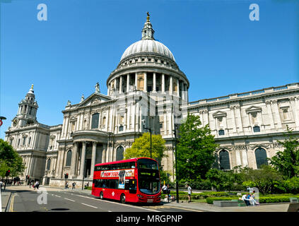 St Paul's Cathedral from South Transept side, under clear blue sky with London Red Bus passing - Stock Photo