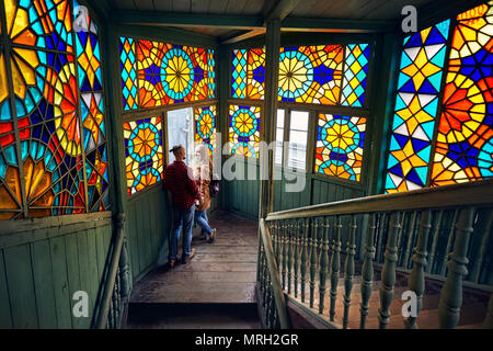 Romantic couple of tourist at balcony with stairs and colorful mosaic glasses in old Tbilisi, Georgia. - Stock Photo