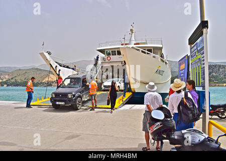 The ferry from Lixouri to Argostoli unloading vehicles & passengers while new passengers wait to board on the harbourside. - Stock Photo