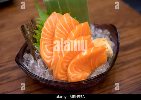 Salmon sashimi with vegetable and ice in a bowl, served in a restaurant - Stock Photo