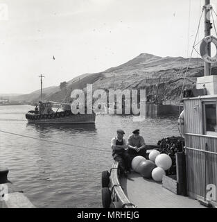 1950s, historical picture of a small fishing boat or drifter coming into a sea opening or inlet near the seaside town of Whitby, North Yorkshire, England, UK. The town was known in this era for its herring fishing and the fishermen used drift-nets as seen on the boat in the foreground. - Stock Photo