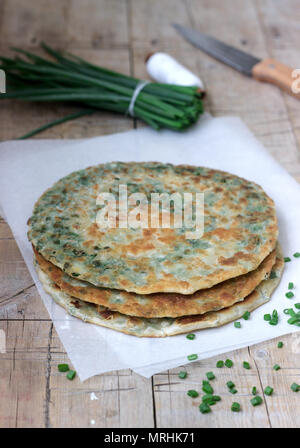Homemade appetizing scallion pancakes and a bunch of green onions. Rustic style. - Stock Photo