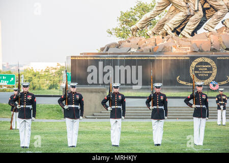 The U.S. Marine Corps Silent Drill Platoon performs during a sunset parade at the Marine Corps War Memorial, Arlington, Va., June 13, 2017. Sunset parades are held as a means of honoring senior officials, distinguished citizens and supporters of the Marine Corps. (U.S. Marine Corps photo by Lance Cpl. Hailey D. Clay) - Stock Photo