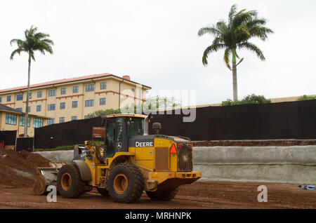 SCHOFIELD BARRACKS, Hawaii — A construction tractor rests in the dirt between its barrier and the clinic buildings that stand tall behind it. Swinerton Builders have been excavating and constructing within an area neighboring McCornack Road and the U.S. Army Health Clinic, here, before and after May 24. Employees of the company are manufacturing the new building that will provide a wider range of parking options for soldiers and civilians alike to use while under care at the clinic. - Stock Photo