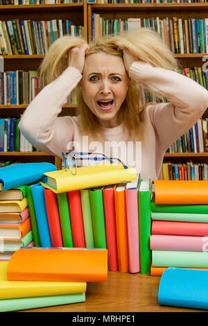 Angry woman yelling, Caucasian girl with long hair, screaming with fury in the library - Stock Photo