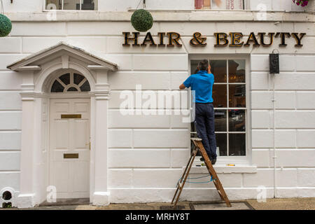 A workman on a ladder repairing a window outside a hair and beauty shop in Canterbury, Kent, England, UK. - Stock Photo