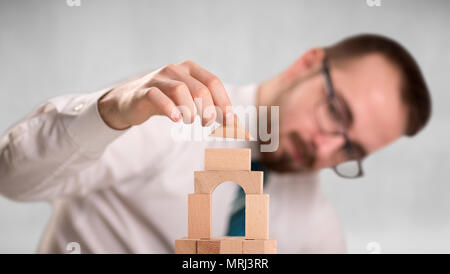 Young handsome businessman using wooden building blocks  - Stock Photo