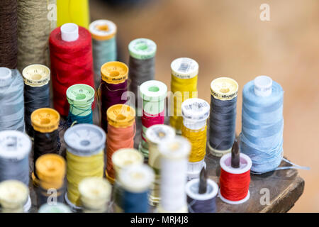 Colourful cotton bobbins and thread in a traditional tailors shop in the UK - Stock Photo