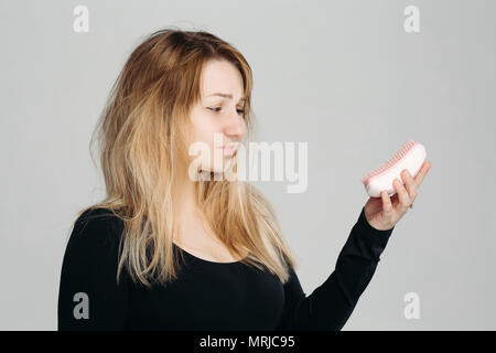 Young confused girl with messy blonde hair. - Stock Photo