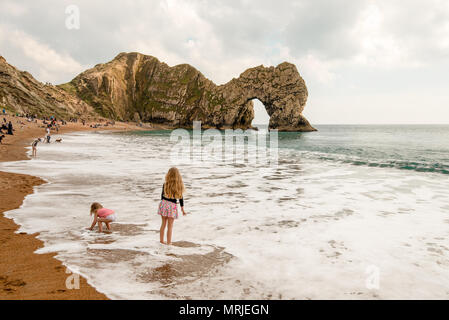 Children play on the beach and in the small waves in the foreground of the tourist attraction Durdle Door, a limestone arch along the Jurassic Coast,  - Stock Photo