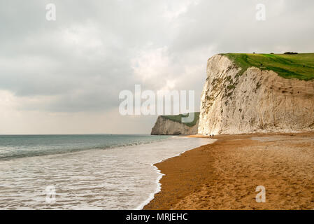 A sun beam lights up some of the shear White cliffs along Dorsets Jurassic Coast with the South West Coatal Path running along the top of them. Lulwor - Stock Photo