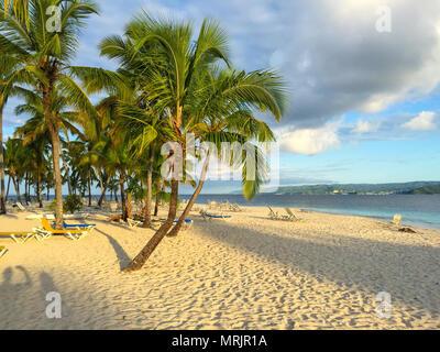 Beach Caribbean Sea, beautiful sandy beach, palms and sunbeds, shadow of the sun - Stock Photo
