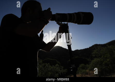 Photographer Ruben Dario Betancourt uses a 500mm Canon F4 lens and sunglasses, in the Cuenca los Ojos reserve. Natural reserve,. Sunset, Sun, sunset