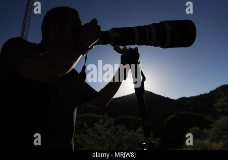 Photographer Ruben Dario Betancourt uses a 500mm Canon F4 lens and sunglasses, in the Cuenca los Ojos reserve. Natural reserve,. Sunset, Sun,sunset