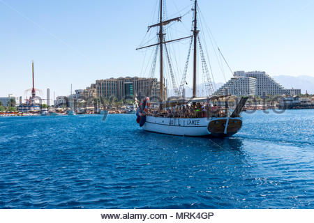 The excursion boat L'Amie cruises in the Gulf of Aqaba off the resort city of Eilat in southern Israel. The hills of Aqaba, Jordan are in the backgrou - Stock Photo