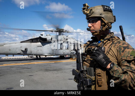 Staff Sgt. Abel Contreras, communications chief with the 31st Marine Expeditionary Unit's Force Reconnaissance Platoon (FRP), waits to board an MH-60S Sea Hawk helicopter aboard the USS Bonhomme Richard (LHD 6) before launching for vessel Visit, Board, Search and Seizure (VBSS) training, June 15, 2017.  During VBSS, Marines with FRP board vessels via rotary-wing aircraft or surface boats in response to a terrorist threat, to interdict pirates and smugglers or to disrupt criminal activity.  The 31st MEU partners with the Navy's Amphibious Squadron 11 to form the amphibious component of the Bonh