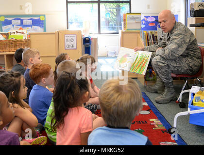"""Col. Roman L. Hund (left), installation commander, reads """"Mister Seahorse"""" by Eric Carle to children at the Child Development Center June 12. Hund was invited to read to children by CDC officials. (U.S. Air Force photo by Linda LaBonte Britt) - Stock Photo"""