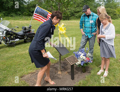"""Shelly Raynes unveils a plaque in front of a tree dedicated to her late husband, retired Tech. Sgt. John A Raynes, during a Memorial Park Dedication Ceremony at Hanscom Air Force Base, Mass., June 16, while John Jr., Ashley and Hannah Grace look on. Raynes worked for Security Forces, Public Affairs and Civil Engineering during his tenure at Hanscom. Also honored during the event was Dana E. Kirane and Dennis """"Dennie"""" Guthrie. (U.S. Air Force photo by Jerry Saslav) - Stock Photo"""