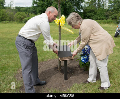 """Jackie Guthrie unveils a plaque in memory of her late husband, Dennis """"Dennie"""" Guthrie, with help from Steve Schofield, a member of the 66th Civil Engineering Division, during a Memorial Park Dedication Ceremony at Hanscom Air Force Base, Mass., June 16. Guthrie worked for the 66th Civil Engineering Division as a heating, ventilation and air conditioning technician. Also honored during the event were Dana E. Kirane and retired Tech. Sgt. John A. Raynes. (U.S. Air Force photo by Jerry Saslav) - Stock Photo"""