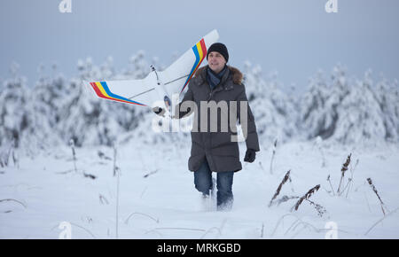 happy man walking on snow winter with rc plane model - Stock Photo