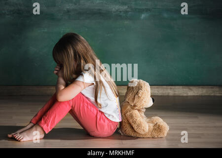 Little girl with teddy bear sitting on floor in empty room. Autism concept - Stock Photo