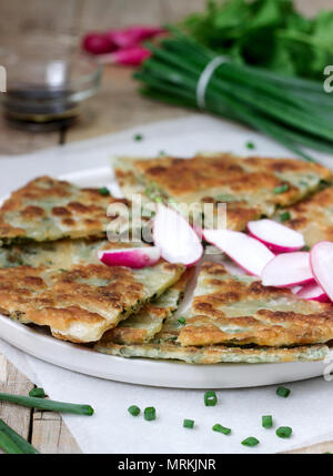 Homemade appetizing scallion pancakes with a bunch of green onions and radishes. Rustic style. - Stock Photo