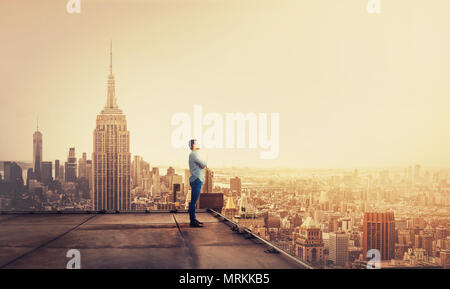 Side view of a thoughtful young businessman standing on concrete rooftop of a skyscraper watching over the big city at sunset. Business research conce - Stock Photo