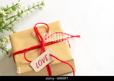 Gift box and flower, paper tag LOVE texting and copy space - Stock Photo