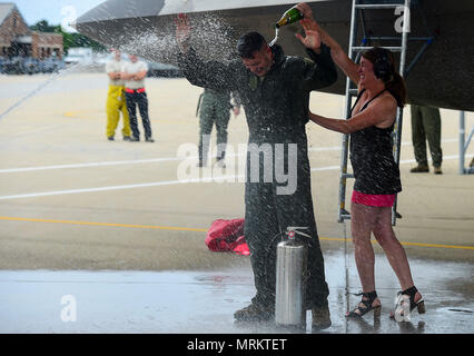U.S. Air Force Col. Peter Fesler, 1st Fighter Wing commander, has champagne poured on him by his wife after his fini-flight at Joint Base Langley-Eustis, Va., June 21, 2017. Fesler was joined by family, friends and members of the installation to celebrate his fini-flight. (U.S. Air Force photo/Senior Airman Derek Seifert) - Stock Photo