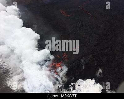 Lava and poisonous sulfur dioxide plumes rise as molten magma reaches the ocean from the eruption of the Kilauea volcano May 24, 2018 in Pahoa, Hawaii. Hot lava entering the ocean creates a dense white plume called 'laze' (short for 'lava haze'). Laze is formed as hot lava boils seawater to dryness. The process leads to a series of chemical reactions that create a billowing white cloud composed of a condensed seawater steam, hydrochloric acid gas, and tiny shards of volcanic glass. The cloud is as corrosive as dilute battery acid, and should be avoided. - Stock Photo