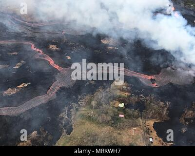 Channelized lava streams down fissure 22 in the East Rift Zone from the eruption of the Kilauea volcano May 23, 2018 in Pahoa, Hawaii. - Stock Photo