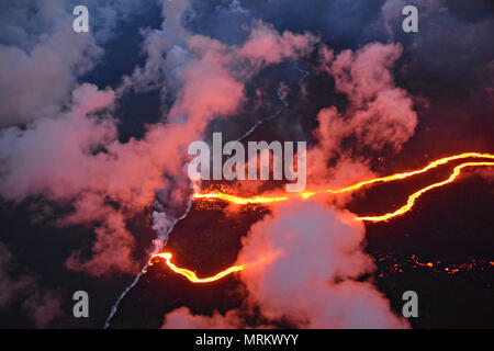 Channelized lava streams down the East Rift Zone from the eruption of the Kilauea volcano into the ocean May 23, 2018 in Pahoa, Hawaii. - Stock Photo