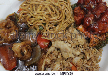 Dinner plate containing Hakka-style shrimp with black bean sauce, General Tao Chicken, chicken fried rice and fried noodles with shrimp. Hakka-style i - Stock Photo
