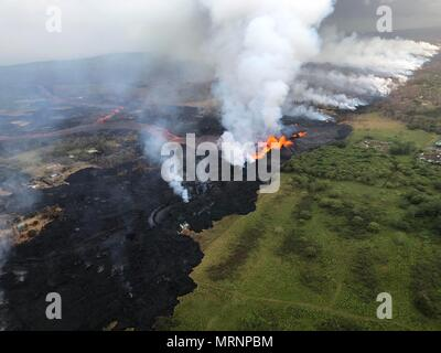 Channelized lava streams down fissure 22 in the East Rift Zone from the eruption of the Kilauea volcano May 21, 2018 in Pahoa, Hawaii. - Stock Photo