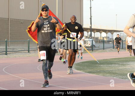 U.S. Army Sgt. 1st Class Ed Rosado, U.S. Army Central Retention counselor, celebrates at the finish line of the Army's 242nd Birthday 5K race, June 14, at Camp Arifjan, Kuwait. This year's birthday celebration emphasizes readiness as its number one priority, meeting its goal to be ready for any challenge worldwide. - Stock Photo
