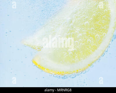 slices of fresh juicy yellow lemon in soda. - Stock Photo