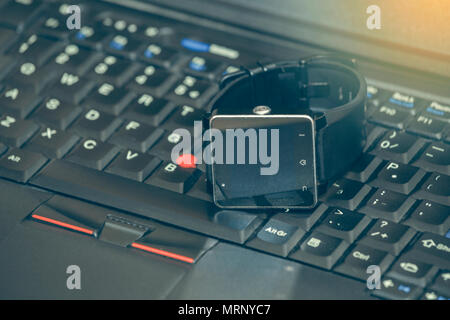 Smart wrist watch laying on a laptop keyboard. Abstract: always stay connected to internet and media. - Stock Photo