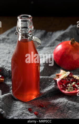 Homemade Sweet Red Pomegranate Grenadine Syrup in a Bottle - Stock Photo